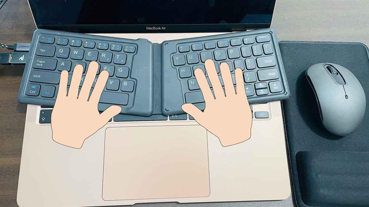 Macbookのキーボードの上にブルーツゥースキーボード