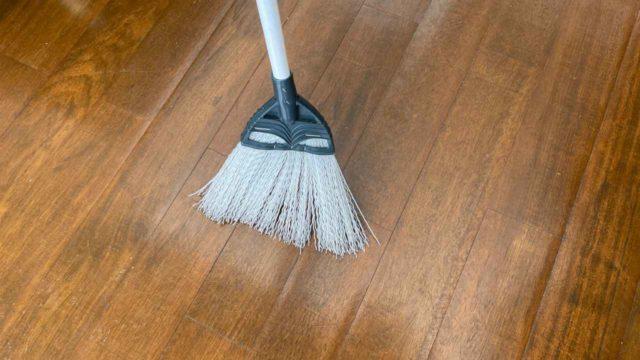 ほうきで床を掃く